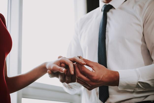 Detailopname. man draagt ring op wifes vinger.