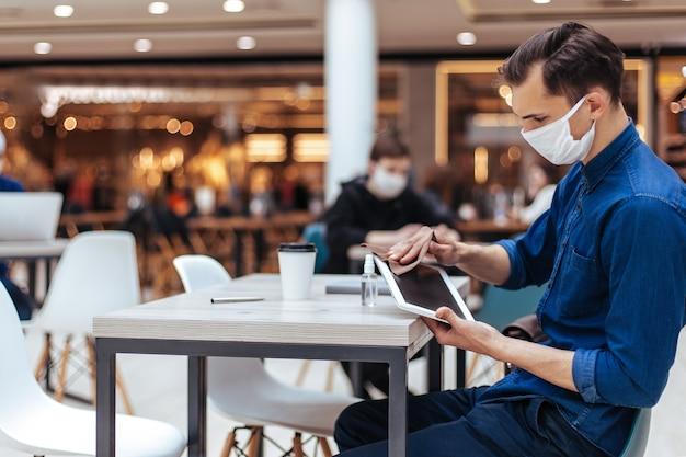 Detailopname . man met een beschermend masker die het scherm van een digitale tablet afveegt met ontsmettingsmiddel.