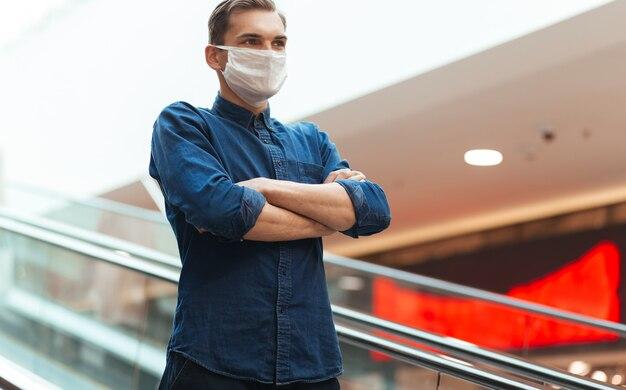 Detailopname. man met een beschermend masker die op de trappen van de metroroltrap staat.