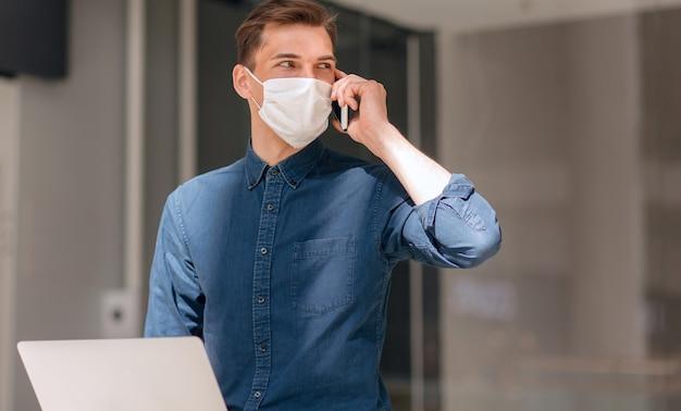 Detailopname. man praten op een mobiele telefoon in de buurt van een stadsgebouw. concept van bescherming van de gezondheid.