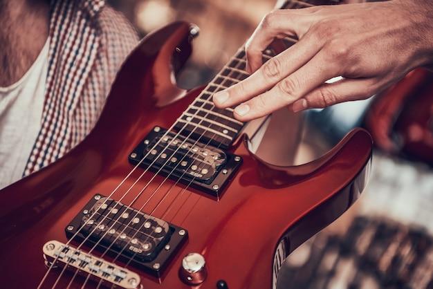 Detailopname. man toont klant op snaren van elektrische gitaar