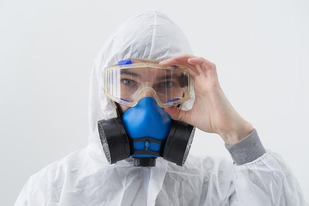 Detailopname. mannelijk ontsmettingsmiddel dat een beschermend pak en een antiviraal masker draagt.