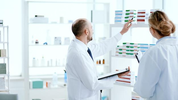 Detailopname. mannelijke apotheker die aantekeningen maakt op het klembord.