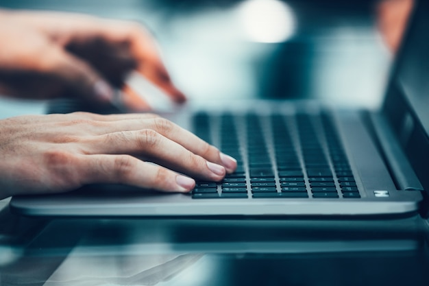 Detailopname. moderne man typen op een laptop toetsenbord.