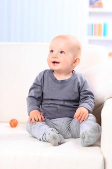 Detailopname. mooie baby zittend op de bank thuis. mensen, kinderen, emoties.