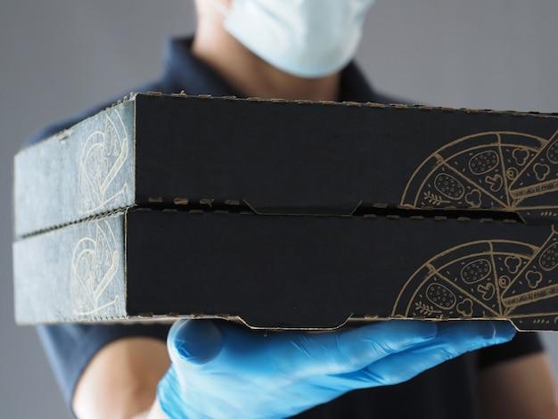 Detailopname. pizza bezorging. twee pizzadoos. levering man met kartonnen dozen in medische rubberen handschoenen. quarantaine.