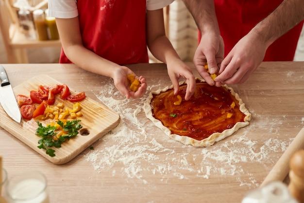 Detailopname. pizza die met groentenplakken voorbereidingen treft.