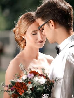 Detailopname. portret van gelukkig jonggehuwden op onscherpe achtergrond.