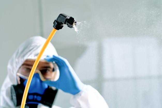 Detailopname. professioneel mannelijk ontsmettingsmiddel in een biogevaarlijk kostuum dat veiligheidsbril aanpast.