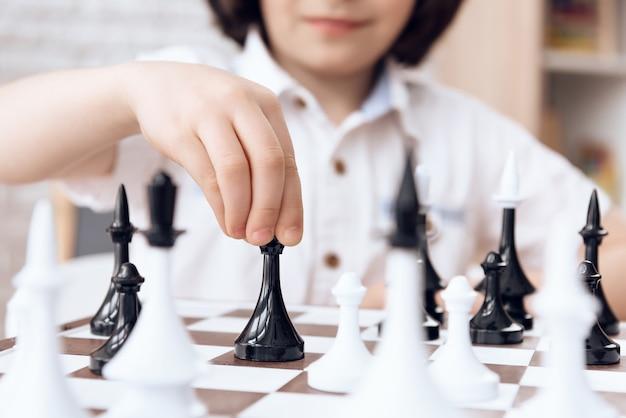 Detailopname. slimme jongensbeweging door bisschop. schaakspel.