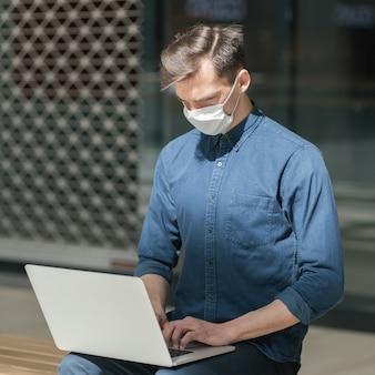 Detailopname. stadsman met een beschermend masker werkt op een laptop. concept van gezondheidsbescherming.