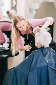 Detailopname. stylist doet haar voor een oudere vrouw cliënt. het concept van levensstijl