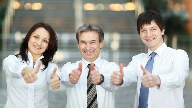 Detailopname . succesvol commercieel team dat een duim omhoog houdt. foto met kopieerruimte