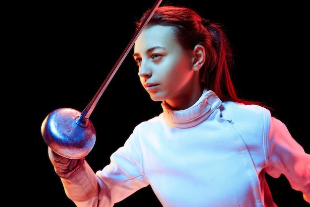 Detailopname. tienermeisje in hekwerkkostuum met in hand zwaard geïsoleerd op zwarte achtergrond, neonlicht. jong model oefenen en trainen in beweging, actie. copyspace. sport, jeugd, gezonde levensstijl.