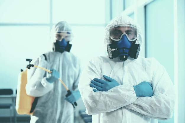 Detailopname. twee mannelijke ontsmettingsmiddelen verlaten de gedecontamineerde kamer. concept van bescherming van de gezondheid.