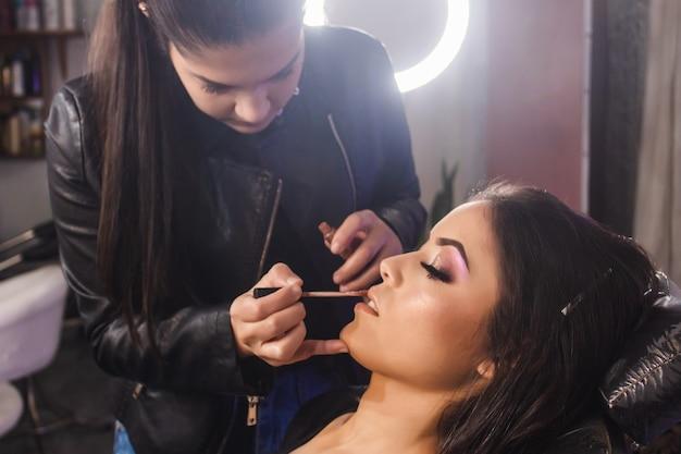Detailopname van een geconcentreerde visagist die de lippen van een mooie jonge vrouw in de schoonheidssalon schildert.