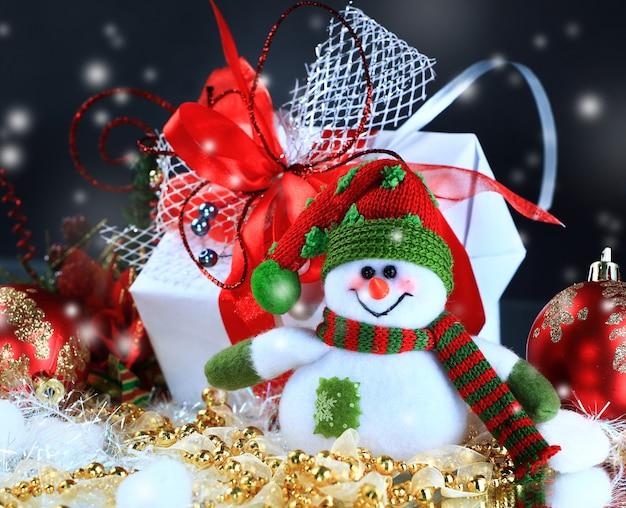 Detailopname. vrolijke sneeuwpop op de achtergrond van kerstcadeaus