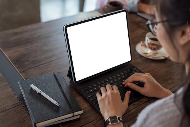 Detailopname. vrouw hand typen op digitale tablet toetsenbord met leeg scherm op bureau op kantoor.