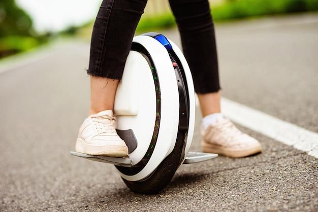 Detailopname. vrouwelijke benen op een monocycle.