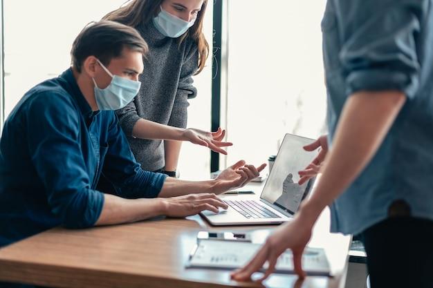 Detailopname. werknemers met beschermende maskers die online informatie bespreken