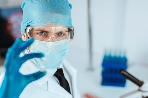 Detailopname. wetenschapper die een capsule met een nieuw vaccin bekijkt. wetenschap en gezondheid.
