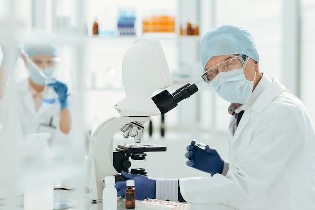 Detailopname. wetenschapper met behulp van een microscoop in een biochemisch laboratorium. wetenschap en gezondheid.