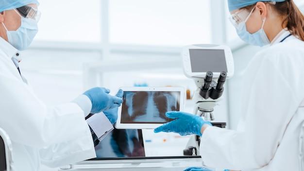 Detailopname. wetenschappers in beschermende maskers die de resultaten van testen bespreken. concept van de gezondheidszorg.