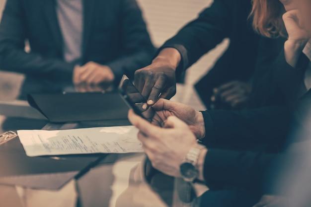Detailopname. zakelijke collega's die berichten op een smartphone bekijken. mensen en technologie