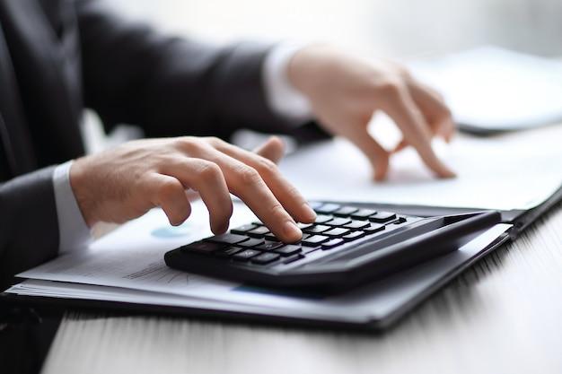 Detailopname. zakenman controleert de financiële gegevens met rekenmachine.
