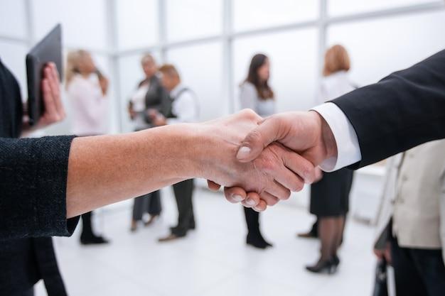 Detailopname. zakenman en zakenvrouw die de deal bevestigen met een handdruk