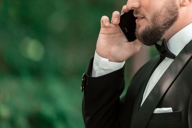 Detailopname. zakenman praten over zijn smartphone op een straat in de stad
