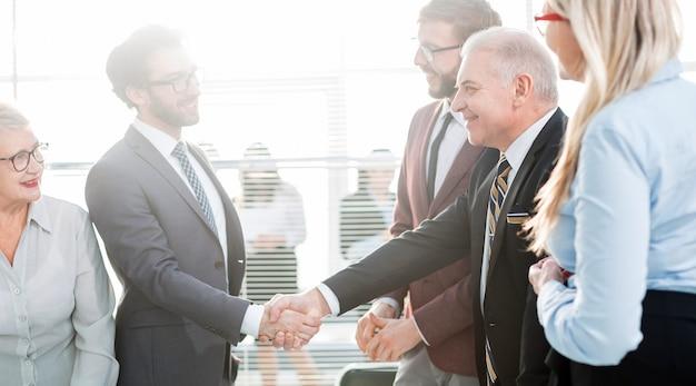 Detailopname. zakenpartners handen schudden alvorens onderhandelingen te beginnen.