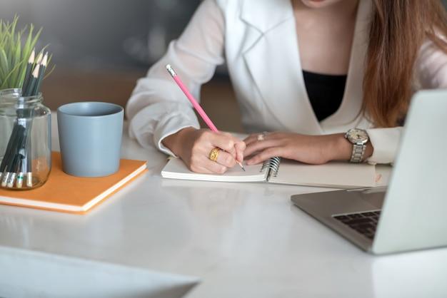 Detailopname. zakenvrouw schrijven op een lege notebook op de tafel op kantoor.