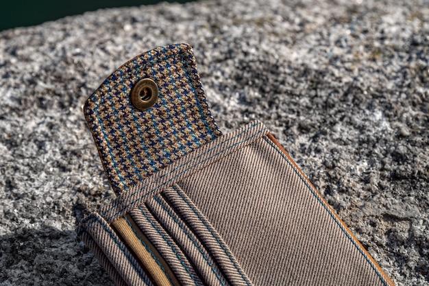 Details en elementen van handgemaakte portemonnee van bruin leer en geruit textiel op steen