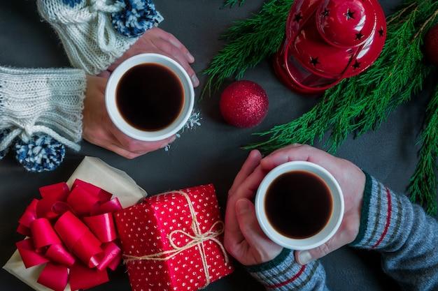 Details van de handen van vrouwen en mannen met een kopje koffie op de tafel met kerst decora