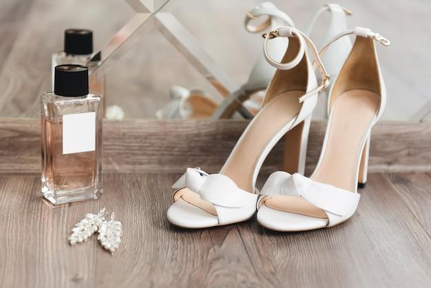 Details van de trouwdag. bruidschoenen op een lichte hoogste mening als achtergrond
