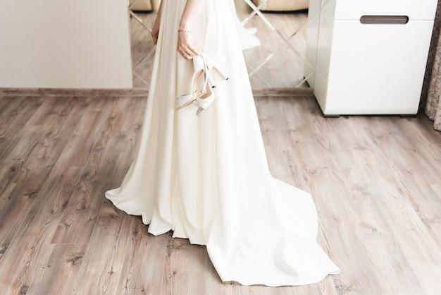Details van de trouwdag. schoenen in de handen van de bruid