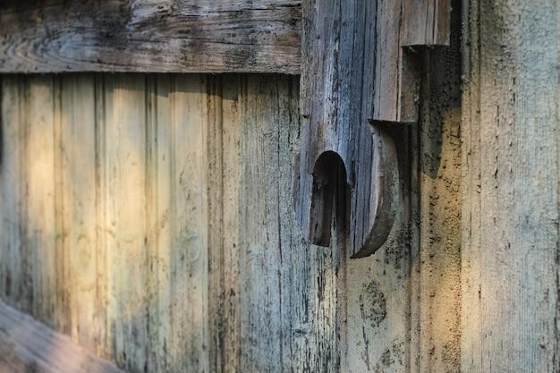 Details van een oud vintage houten huis met een houten muur in grunge-stijl. close-up en selectieve focus met kopieerruimte. vintage achtergrond voor ruimtedecoratie