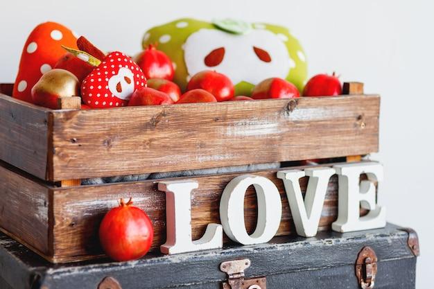 Details van het interieur - appels van stof, houten doos in shabby chic-stijl en letters liefde