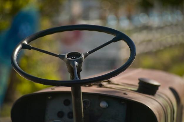 Details van het stuur en de instrumentatie van een oude landbouwtractor genesteld op het platteland tijdens een werkdag.
