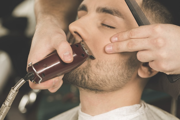 Details van het trimmen. bijgesneden close-up van een kapper bijgesneden baard aan zijn cliënt