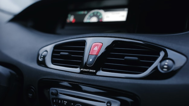 Details van het voorpaneel van de auto met luchtverspreiders en een noodstopknop