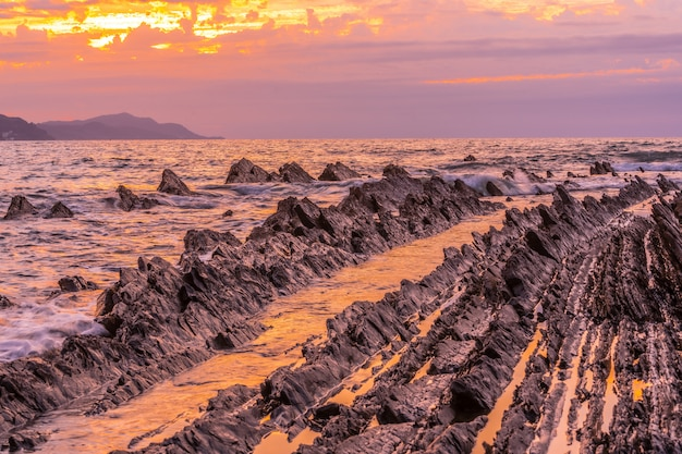 Details van stenen bij zonsondergang van het geopark genaamd flysch op het sakoneta-strand in de stad deba, aan de westkant van het baskische kustgeopark, guipúzcoa. baskenland