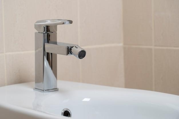 Details van witte keramische bidet met waterkraan in moderne badkamer met beige tegels achtergrond. eenvoudig stijlvol en modern interieurontwerp. detailopname