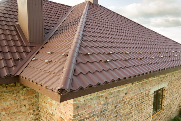Detailweergave van het dak van het huis bedekt met bruine metalen tegelplaten