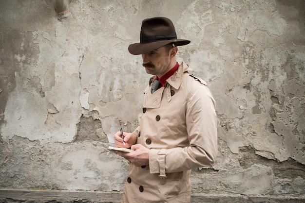 Detective die op een notitieboekje schrijft terwijl tegen een oude muur stadning