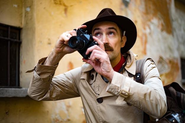 Detective neemt foto's in een sloppenwijk met zijn vintage camera
