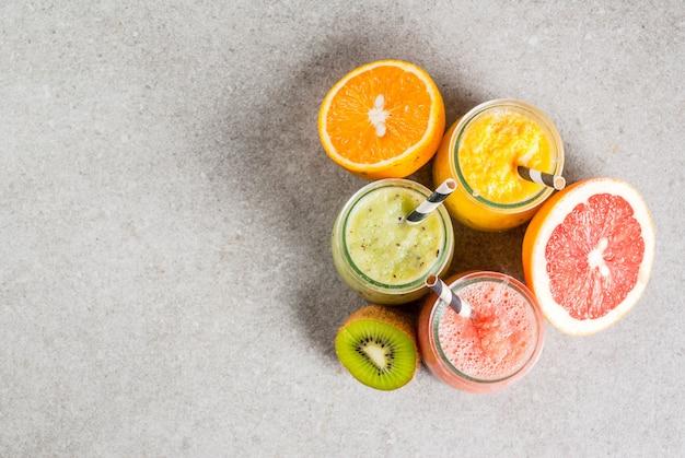 Detox biologische dieetdranken, zelfgemaakte tropische smoothies - kiwi, sinaasappel, grapefruit, in geportioneerde potten, met ingrediënten, op een grijze stenen tafel. copyspace bovenaanzicht
