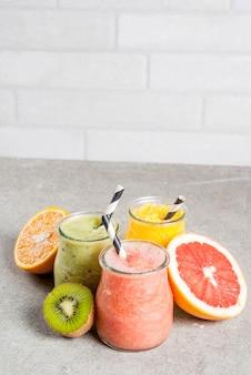 Detox biologische dieetdranken, zelfgemaakte tropische smoothies - kiwi, sinaasappel, grapefruit, in geportioneerde potten, met ingrediënten, op een grijze stenen tafel. copyspace