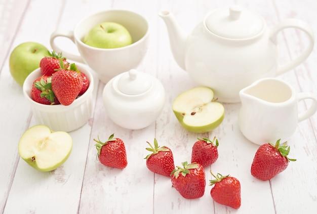Detox concept. lekker fruit en bessen. gezond eten. veganisme, vegetarisme, rauwkostdieet. aardbeien en appels. zomer vers fruit. kopieer ruimte. vitaminen in voedsel. gezond ontbijt. thee set